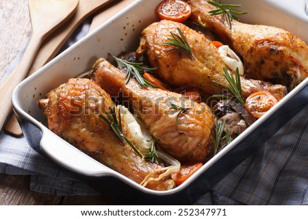 chicken legs with rosemary in a baking dish close-up on the table. horizontal  - stock photo