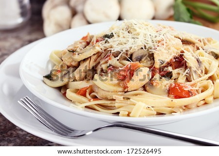 Chicken linguine with grilled chicken, tomatoes, mushrooms and freshly grated parmesan cheese. Fresh mushrooms and herbs in background. - stock photo
