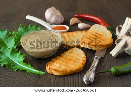 Chicken liver pate on bread and in jar - stock photo