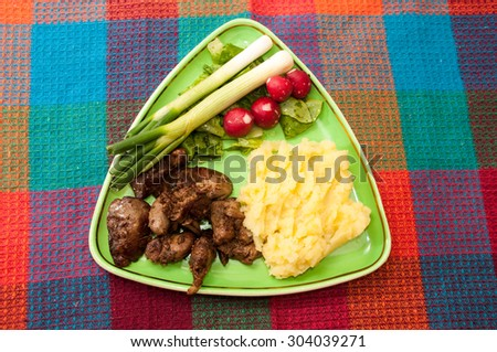 Chicken liver served with mashed potatoes, onions and radishes. - stock photo