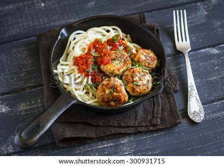 chicken meatballs and spaghetti in a pan on a  dark wooden background - stock photo