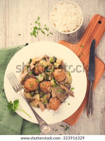 Chicken meatballs with oyster mushrooms, zucchini and rice on white plate and wooden cutting board.  Healthy food concept.  Top view. Retro style toned. - stock photo