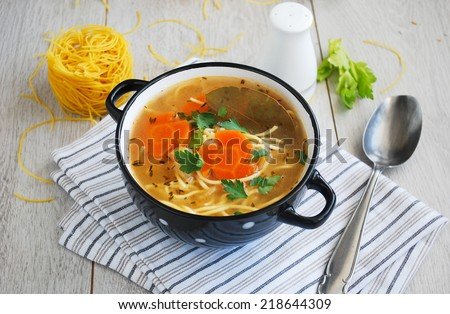 Chicken noodle soup in black and white polka dot bowl - stock photo