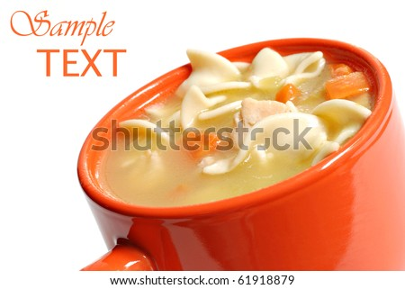 Chicken noodle soup in bright orange mug on white background with copy space.  Macro with shallow dof. - stock photo