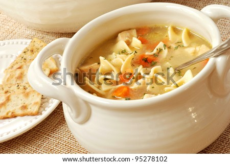 Chicken noodle soup in cream colored ceramic bowl with handles.  Plate of crackers and soup tureen in background.  Closeup with shallow dof. - stock photo