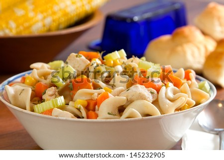 Chicken Noodle Soup with corn, butter and bread in the background
