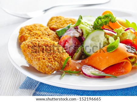 chicken nuggets and vegetable salad on a plate - stock photo