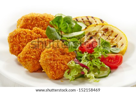 chicken nuggets and vegetables on a white plate - stock photo