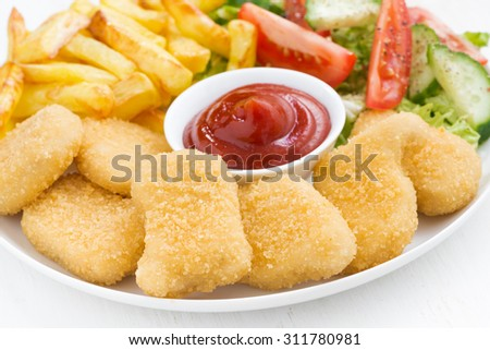 chicken nuggets, french fries and vegetable salad, closeup, horizontal