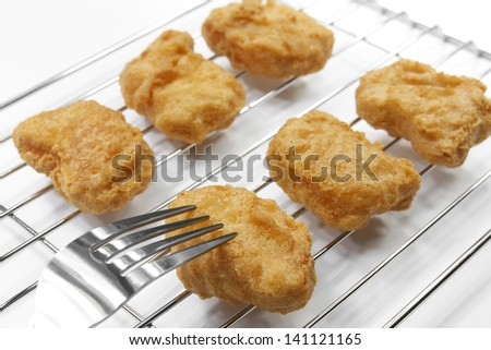 chicken nuggets with fork on grille, white background - stock photo