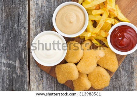 chicken nuggets with french fries and different sauces on board, top view, horizontal - stock photo