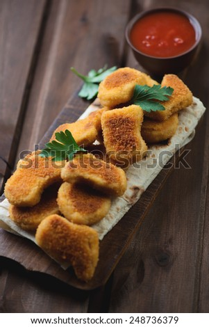 Chicken nuggets with parsley over dark rustic wooden background - stock photo