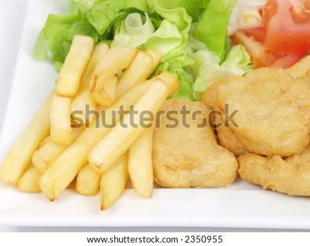chicken nuggets with salad, tomato, fries and a glass of ice tea