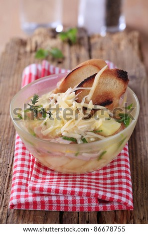 Chicken or garlic soup with grated cheese and ham  - stock photo