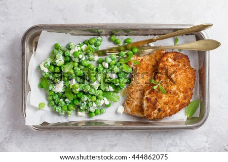 Chicken or pork schnitzel with cheese and  peas salad, selective focus