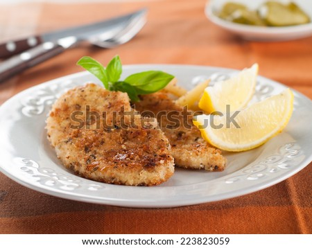 Chicken or pork schnitzel with lemon wedges, selective focus - stock photo