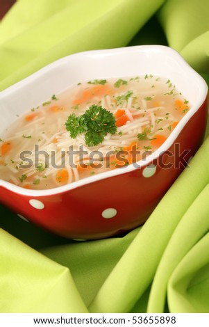 Chicken or turkey soup with carrot, noodles and parsley - stock photo