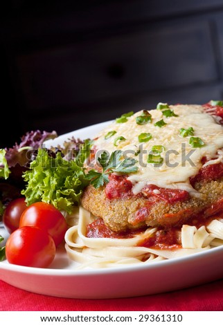 Chicken parmesan or parmigiana, with melting mozzarella and parmesan cheeses, over fettucine ribbon pasta.