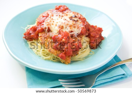 Chicken parmesan with a thick sauce served over pasta - stock photo