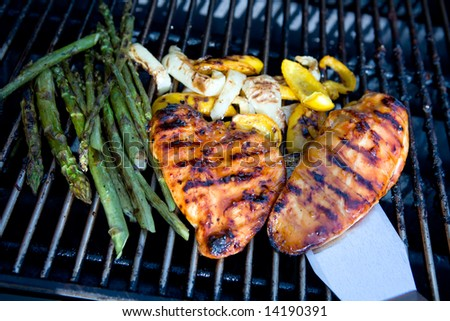 Chicken, peppers and asparagus on a barbecue with a lifter lifting the chicken breast.