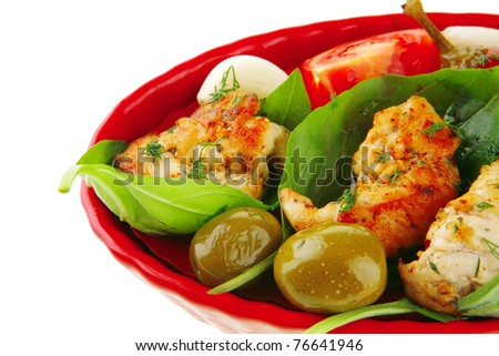 chicken pieces on red dish with tomatoes