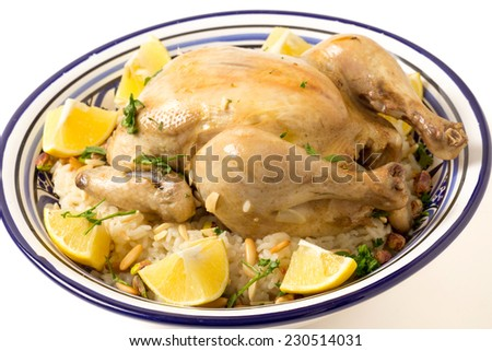 Chicken pilaf, or riz bi djaaj, traditional Arab and Mediterranean boiled chicken and rice dish, served with roasted nuts and lemon wedges. - stock photo
