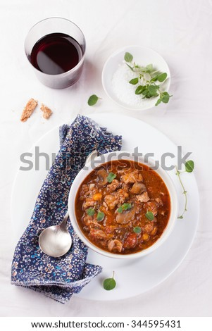 Chicken ragout with pumpkin, mushrooms and oregano stewed in red wine in a white ceramic bowl. Selective focus - stock photo