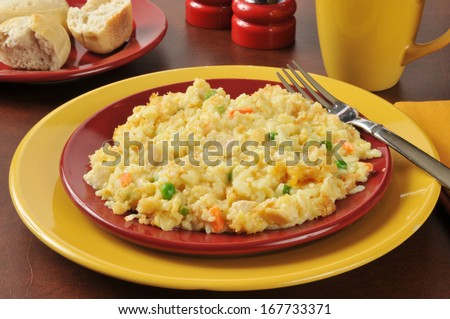 Chicken rice casserole with vegetables and dinner rolls - stock photo