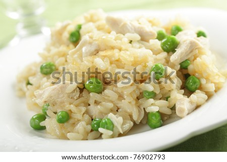 Chicken risotto with green peas on the plate closeup