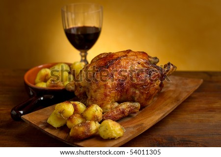 chicken roasted with potatoes on wood background - stock photo