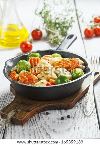 Chicken roasted with vegetables in a frying pan on the wooden table