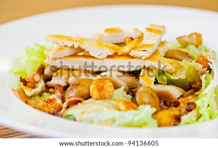 Chicken salad with grated carrots, mushrooms, bread croutons and green lettuce  in the white bowl - stock photo