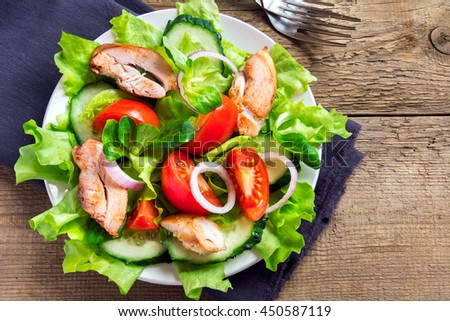 Chicken salad with leaf vegetables and tomatoes over rustic wooden background with copy space - stock photo