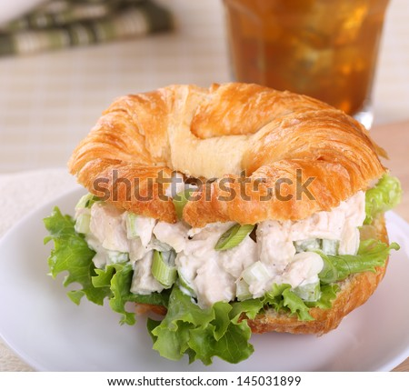 Chicken salad with lettuce on a croissant roll - stock photo