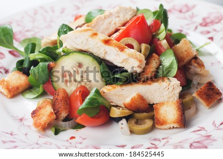 Chicken salad with olives, tomato, croutons, and corn-salad