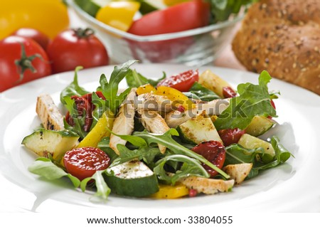 Chicken salad with rocket and vegetables close up - stock photo