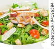 Chicken salad with tomatoes, arugula and bread croutons in the white bowl - stock photo