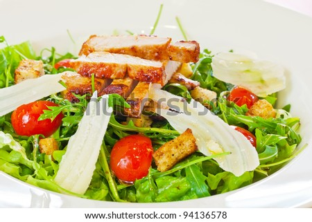 Chicken salad with tomatoes, arugula and bread croutons in the white bowl