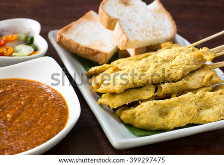 Chicken Satay and toast served with peanut sauce and vegetable salad sauce  on wooden table / Selective focus - stock photo