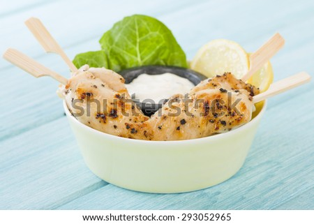 Chicken Satay - Char-grilled spicy mini chicken fillet skewers served with lemon and aioli dip inside a bowl.