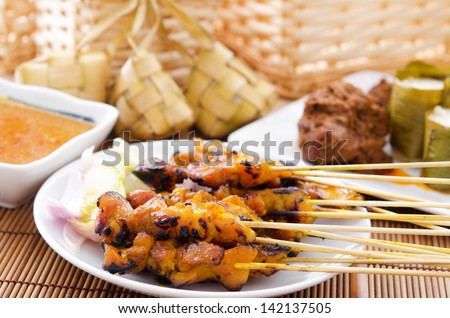Chicken satay, ketupat or malay rice dumpling, lemang, rendang. Traditional Malay food, ramadan dish. Malaysian cuisine. - stock photo