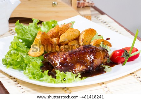 Chicken sauce with fries on green leaf lettuce