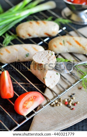 Chicken sausages on the grill with vegetables, spices, sauce