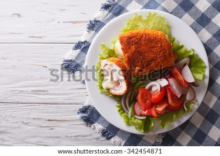 Chicken schnitzel cordon bleu and a salad on a plate on a table. horizontal top view