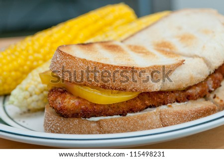 chicken schnitzel sandwich with heirloom tomatoes and cheese on toasted sourdough bread with corn on the cob