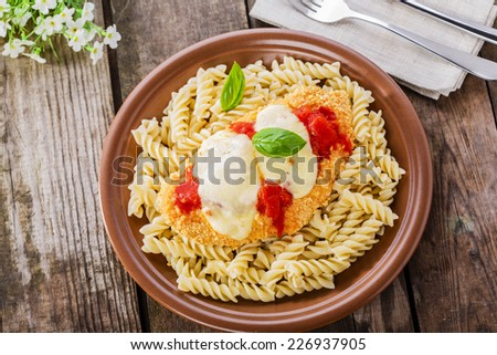 chicken schnitzel with tomato sauce and mozzarella parmesan - stock photo