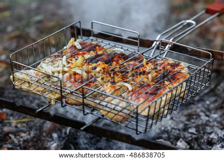Chicken shashlik being roasted over charcoal