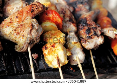 chicken shish kebab on bbq grill in sauce on skewers with tomatoes and peppers - stock photo