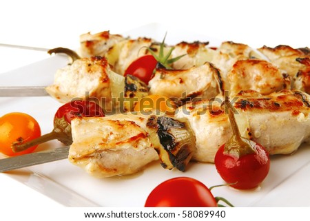 chicken shish kebab on white platter with vegetables - stock photo