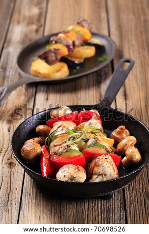Chicken shish kebabs on a skillet - stock photo